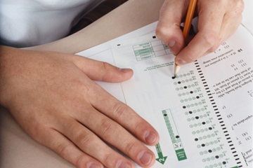 Two hands filling in scantron bubbles